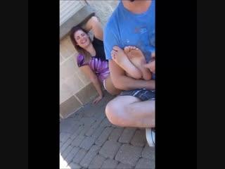 Guy tickles girl's feet in the street