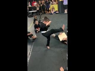 Мальчик пытается разбить доску ногой